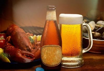 Beer glass and bottle next to a lobster dinner