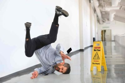 Man falling next to caution wet floor sign