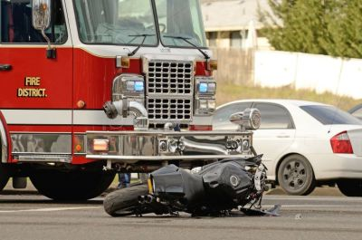 Damaged motorcycle laying on the road and a firetruck close behind it