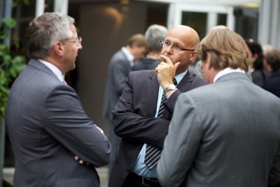 Three men in suits facing each other