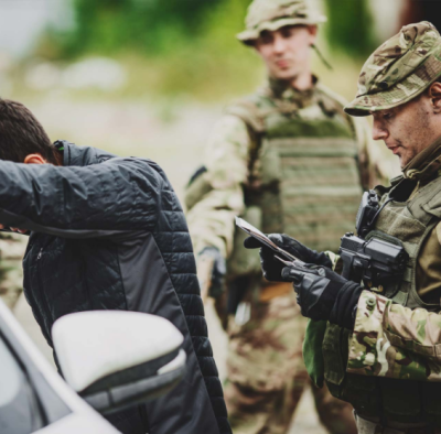 Two men dressed in camoflauge uniforms and man with hands against a car
