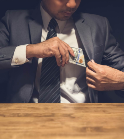 Man in suit putting cash in coat pocket