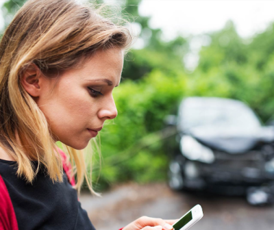 Women looking down at her phone and a damaged car in trees in the background