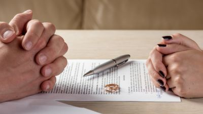 Close up of a man and woman's hands folded on either side of a document with a pen and rings sitting on top