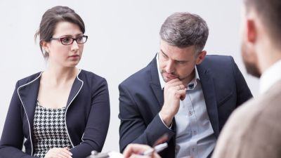 Man and woman sitting across man with a clipboard