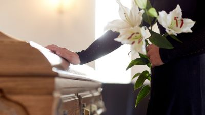 Person with flowers and hand on a casket