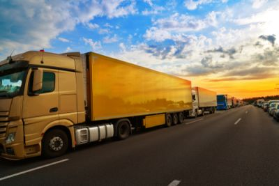 Several yellow semi trucks in a row on a road