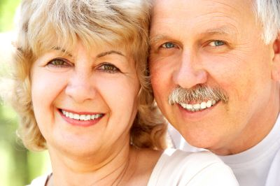 Older man and woman smiling with their heads close together