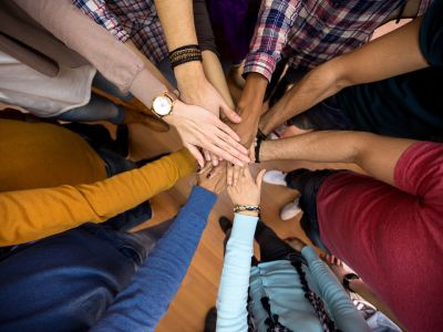 8 people standing in a circle each putting one hand together in the middle