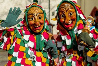 Two masked people dressed in colorful clothing