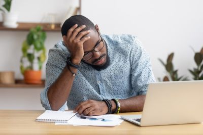Man with hand on his head looking at laptop