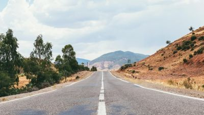 Empty desert road with scenic hills ahead
