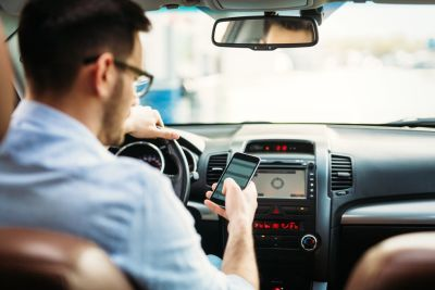 Man sitting in drivers seat with hand on the wheel looking down at his phone