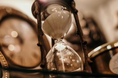Hourglass in front of large clock