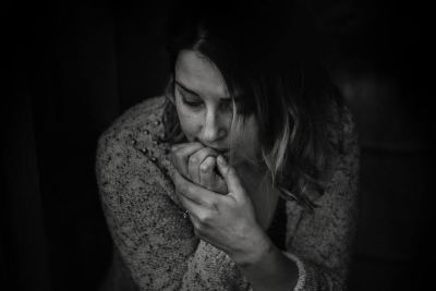 Woman in long sleeved top hunched over biting her nails