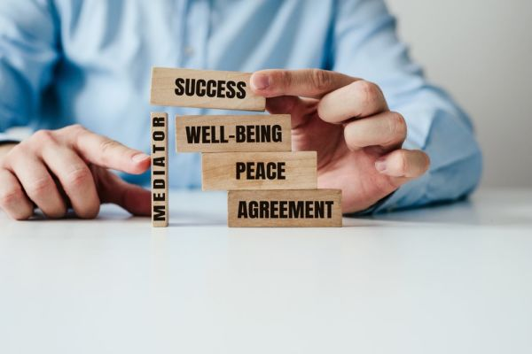 Wood blocks labeled: success, well-being, peace, agreement, and mediation stacked up