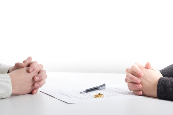 People with clasped hands on a desk over wedding bands and papers