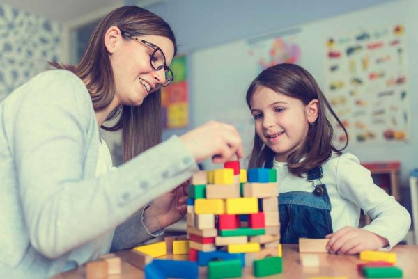 Mother stacking colorful blocks with her daughter
