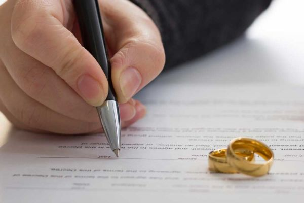 Person signing paper. Two wedding rings rest on the paper
