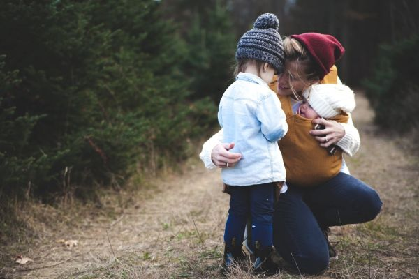 Mother holding her two children in the woods