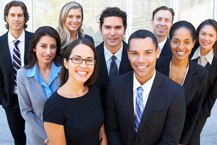 A group of nine business people smile at the camera