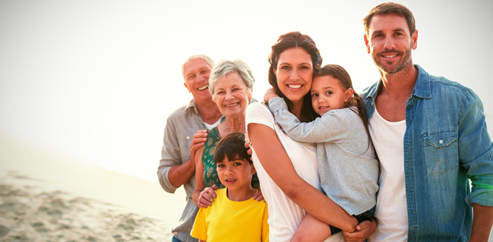 A family of grandparents, parents, and kids smile at the camera