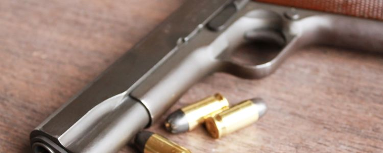 Gun on Desk next to Two Bullets
