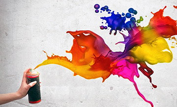 A hand holds a can of spray paint. The paint that comes out is multiple bright colors, and flows dynamically and joyfully in all directions.