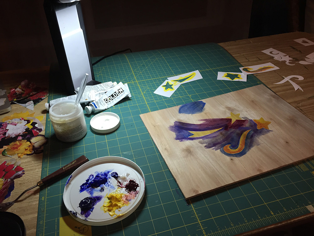 (It's a view of the worktable, with stencils and paints and the practice board.)