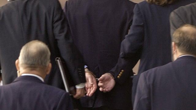 In den USA von grosser symbolischer Bedeutung: der öffentliche Einsatz von Handschellen bei Prominenten., wie hier bei Kenneth Lay, ehemaliger CEO des Energiekonzerns Enron und einer der Hauptverantwortlichen für den Milliardenbetrug beim Gang in den Gerichtssaal im Jahr 2004. Bild: Keystone