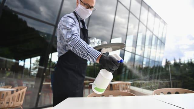 Mehrere Kantone fordern die komplette Öffnung von Gastronomiebetriebe: Ein Kellner desinfiziert den Aussenbereich eines Restaurants. Bild: Shutterstock
