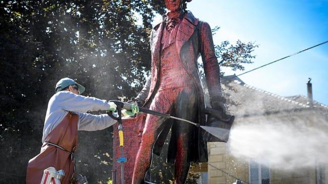 Ein Arbeiter reinigt die beschmierte Statue von David de Pury. Das Denkmal steht seit 1855 in Neuenburg.