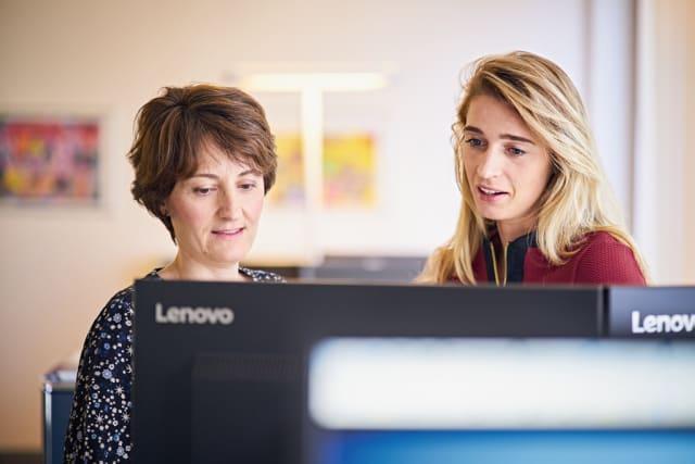 Zwei Frauen vor zwei Computerbildschirmen