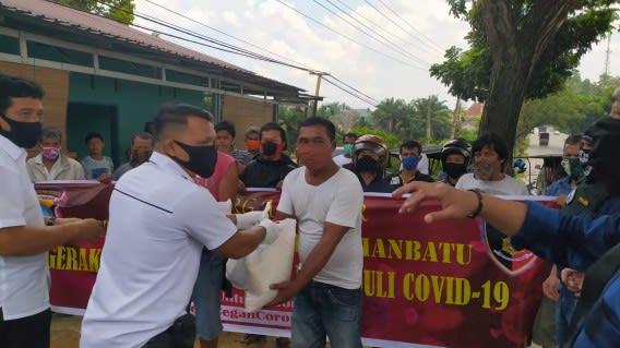 Personil Satreskrim Polres Labuhanbatu menyerahkan bantuan paket Sembako kepada salah seorang abang becak di Rantauprapat