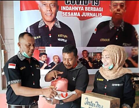 Ketua MCP Labuhanbatu, Ucok Bani alias Uban (kiri) didampingi anggotanya, Erni Manja Hasibuan (kanan), memberikan paket Sembako kepada salah seorang jurnalis media online
