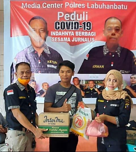 Penasehat MCP Labuhanbatu, Herman alias Ahok (kiri) didampingi anggota, Erni Manja Hasibuan (kanan), saat memberikan paket Sembako kepada salah seorang jurnalis