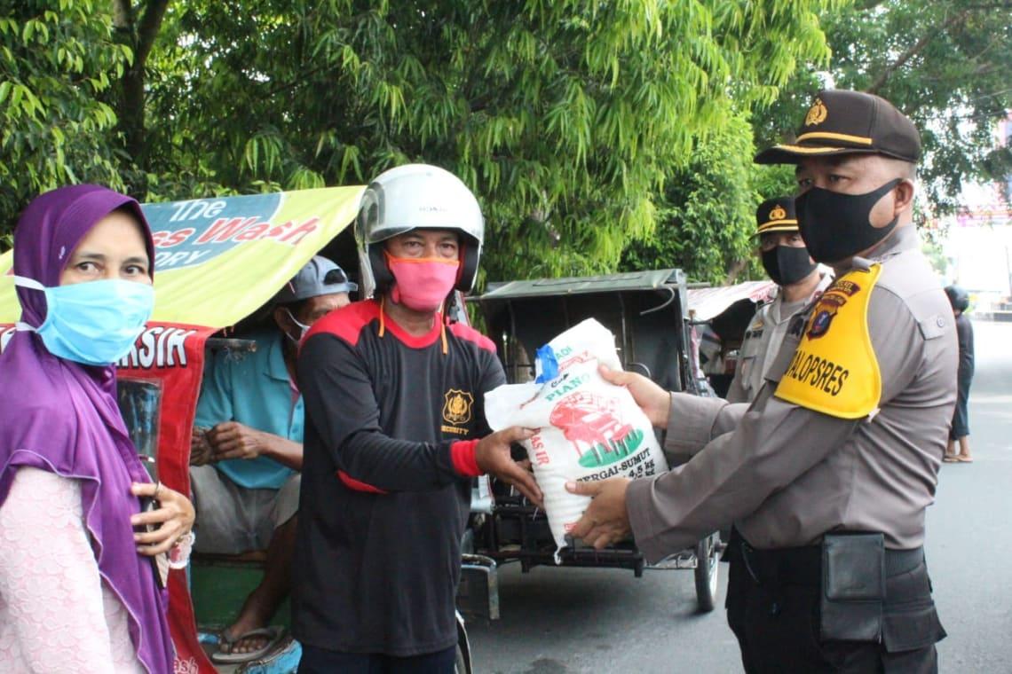 Wakapolres Labuhanbatu, Kompol Muhammad Taufik SE, membagikan beras kepada abang beca