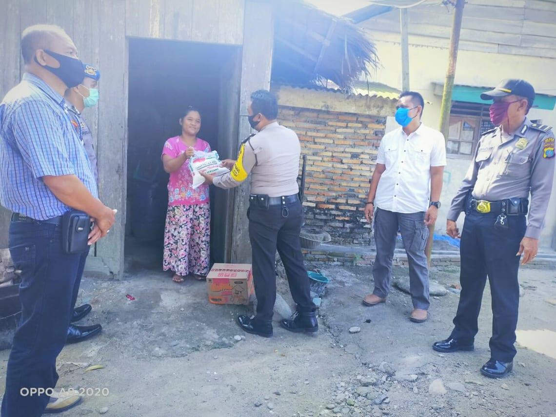 Kapolsek Kampung Rakyat, AKP Eri Prasetyo, bersama sejumlah anggotanya saat memberikan bantuan beras dan mie instant kepada salah seorang warga