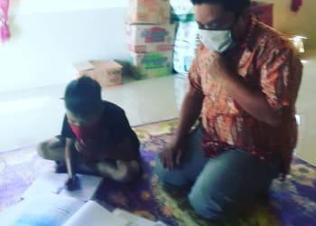 Suardi, guru honorer SD saat mengajar siswa di rumah. Foto :Ist/kompas