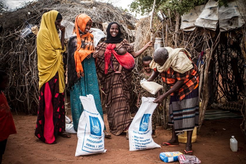 Group of women with a aid bag of food