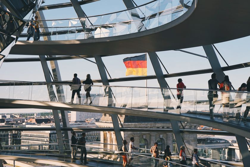 The Reichstag building in Berlin, German flag in the background