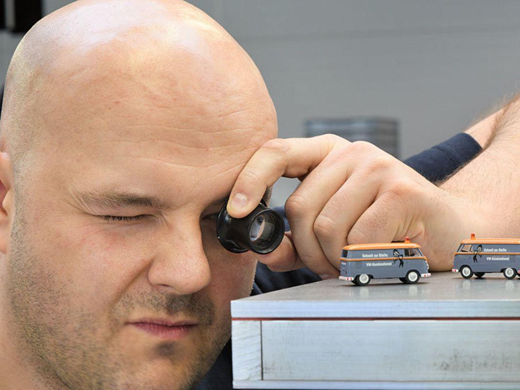 Grzegorz Kotylak kontrolliert aufmerksam die Tampon-Bedruckung am Volkswagen Bulli in 1:87 mit historisch korrekter Werbebeschriftung