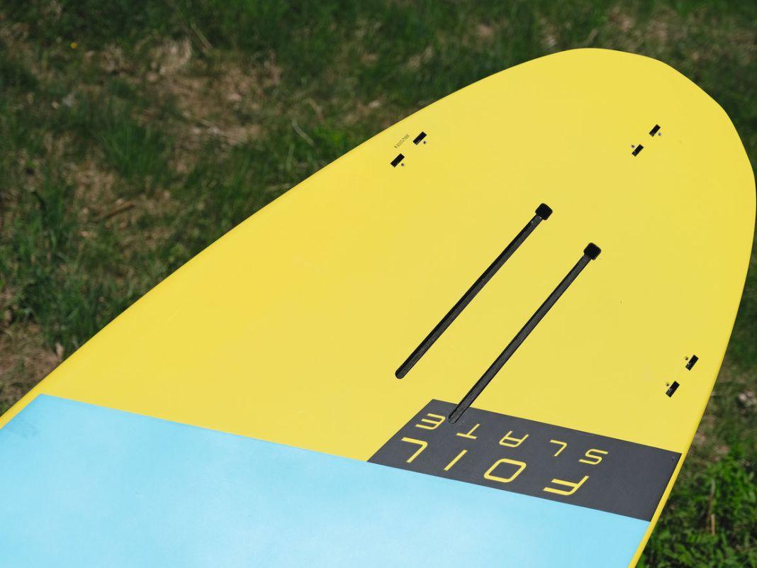 Das Crossoverboard besitzt eine Doppelschiene zur Foil-Montage und Boxen für die FCS-Finnen