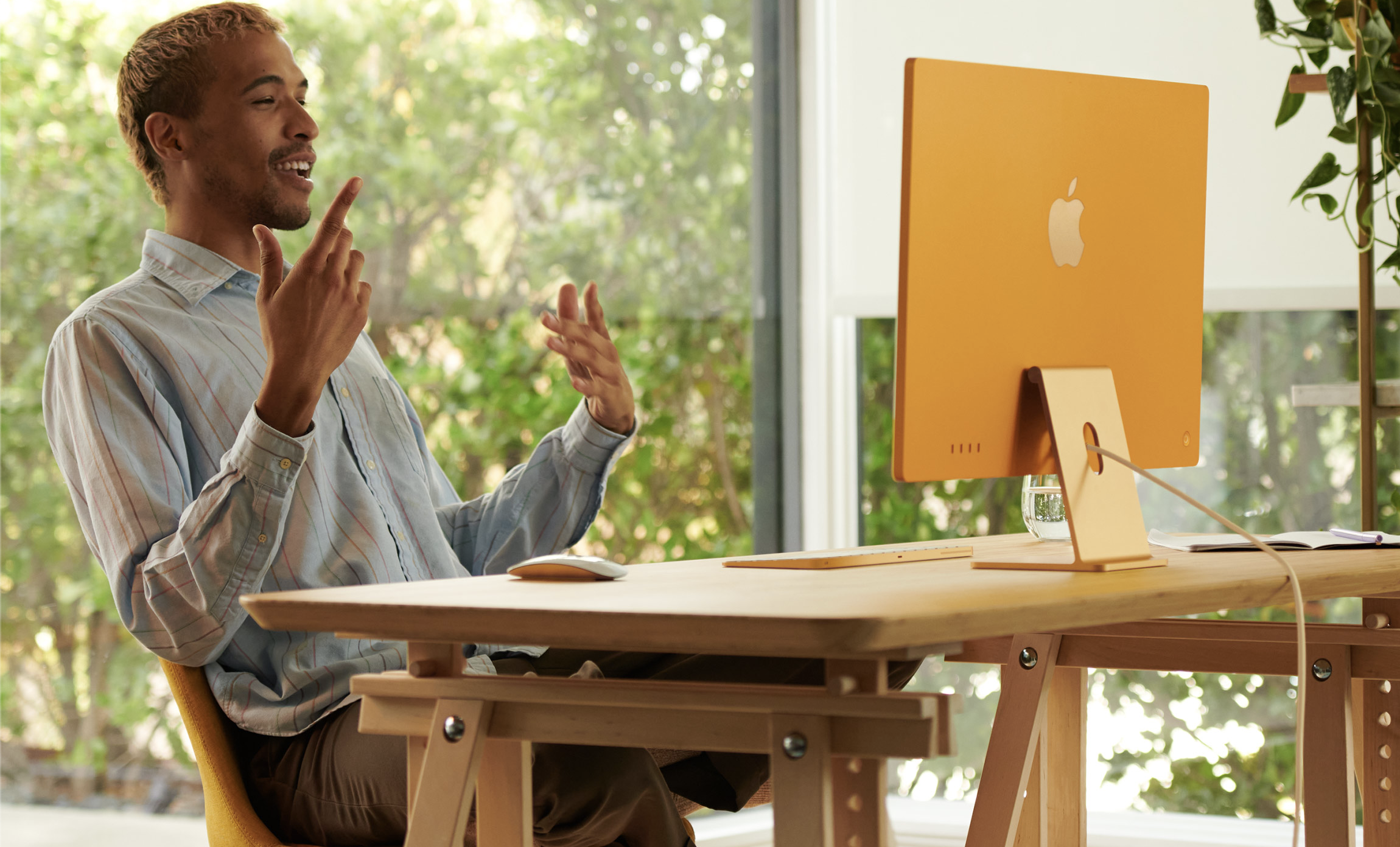 An excited person making hand gestures at a yellow iMac computer