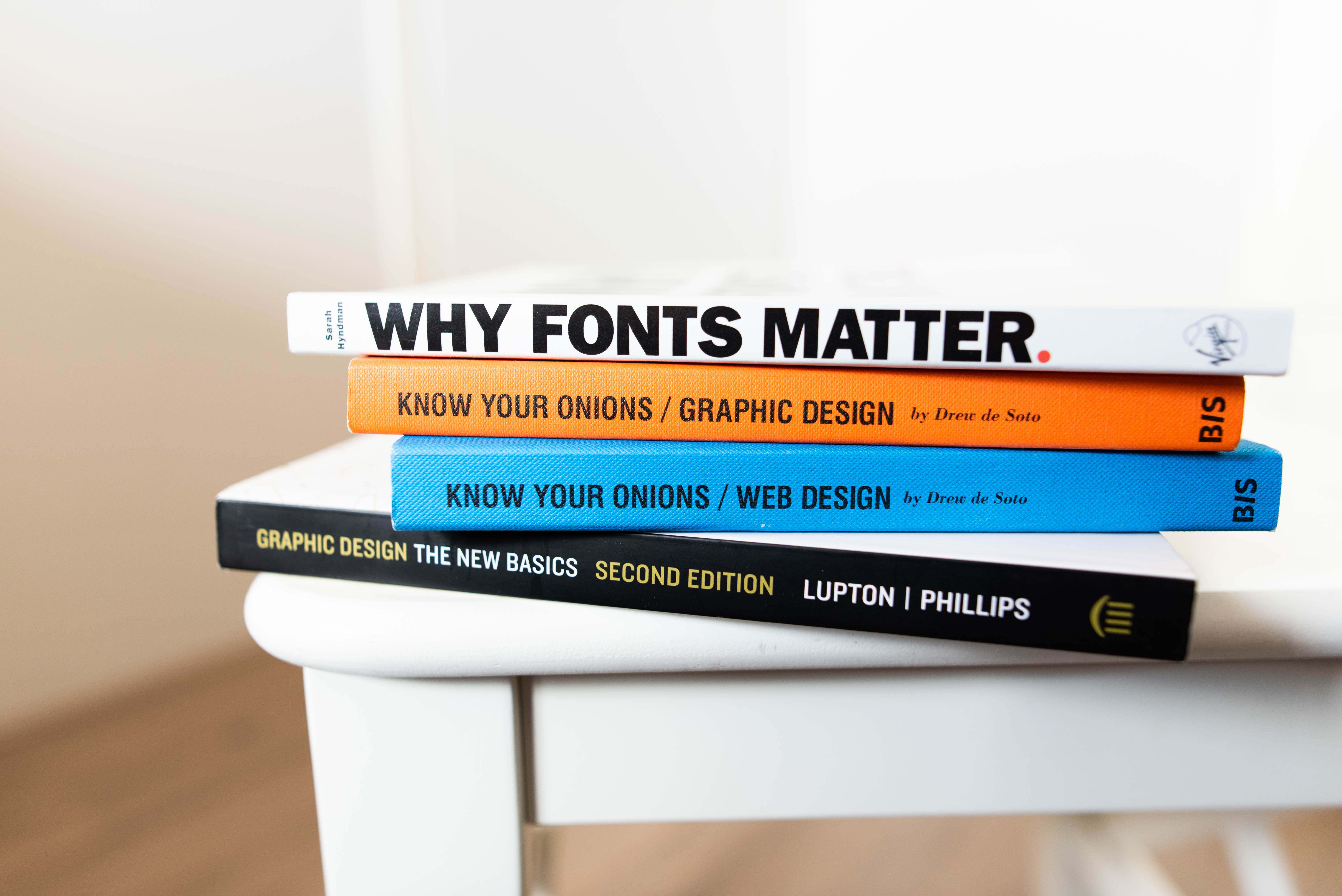Stack of books about design, including one titled 'Why Fonts Matter'