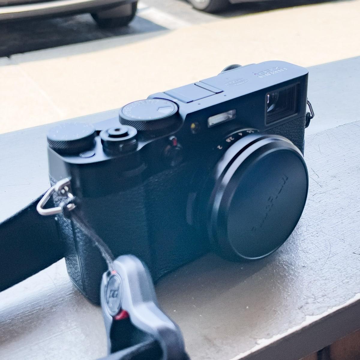 Fuji X100V camera with lens cap and strap