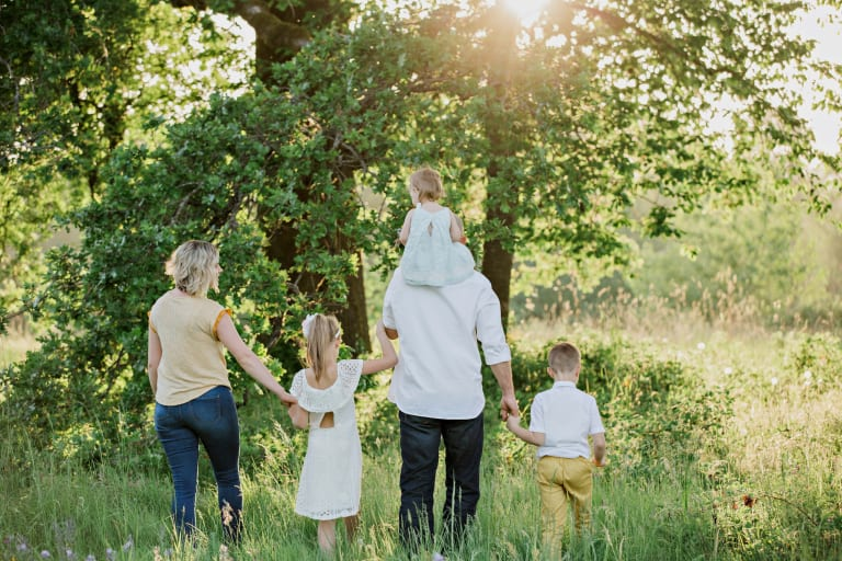 Mutter, Vater und drei Kinder von hintern im Wald, bei Sonnenuntergang.