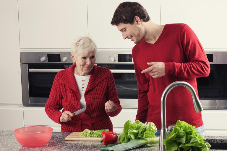 Eine ältere Frau und ein junger Mann kochen zusammen.