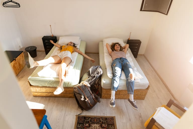Zwei Frauen sind fröhlich mit Rucksäcken bei ihrem Schlafplatz angekommen.