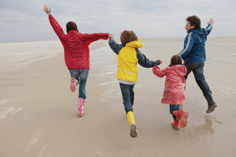 Mutter, Vater und zwei Kinder von hinten, fröhlich springend, an der Nordsee.